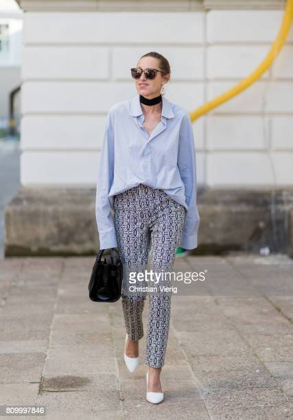 A guest wearing blue button shirt grey pants white heels during the MercedesBenz Fashion Week Berlin Spring/Summer 2018 at Kronprinzenpalais on July...