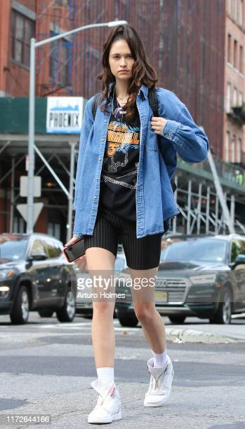 A guest wearing blue denim shirt black printed shirt black shorts and white sneakers during New York Fashion Week on September 05 2019 in New York...