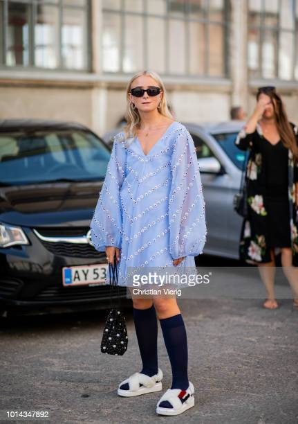 A guest wearing blue dress with v nec fake fur sandals knee socks is seen outside Ganni during the Copenhagen Fashion Week Spring/Summer 2019 on...