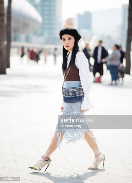 A guest wearing blue high waisted skirt with fringes beret white blouse transparent see through heels is seen at the Hera Seoul Fashion Week 2018 F/W...