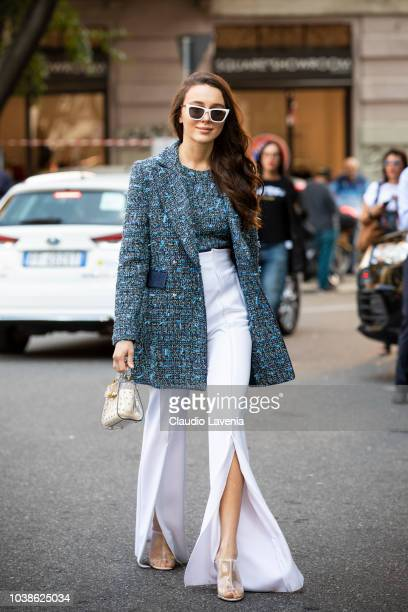 A guest wearing blue jacket and top and white pants is seen before the Giorgio Armani show during Milan Fashion Week Spring/Summer 2019 on September...