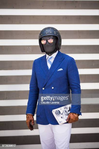 A guest wearing blue jacket black helmet white pants a mask and leather gloves is seen during the 94 Pitti Immagine Uomo at Fortezza Da Basso on June...