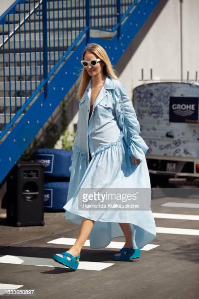Guest wearing blue long dress outside Designer Remix during Copenhagen fashion week SS22 on August 11, 2021 in Copenhagen, Denmark.