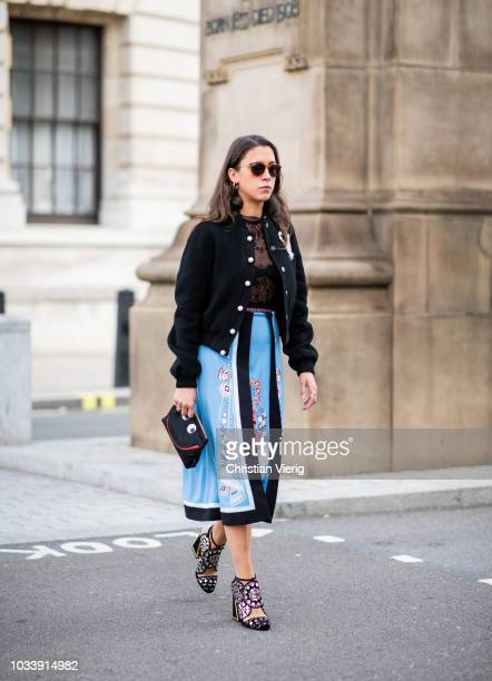 A guest wearing blue skirt with print black jacket sheer top is seen outside Anya Hindmarch during London Fashion Week September 2018 on September 15...