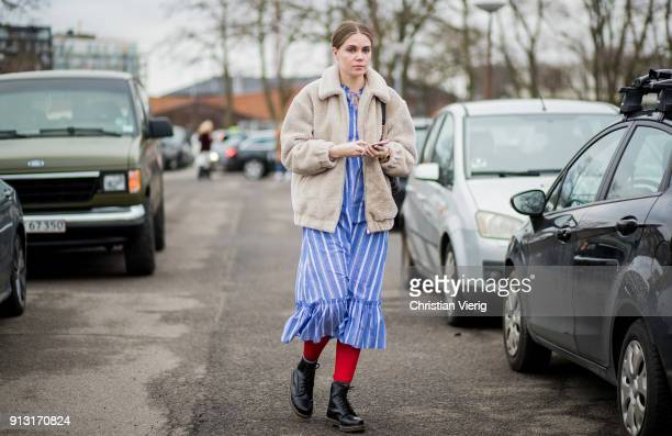 A guest wearing blue striped dress outside Munthe during the Copenhagen Fashion Week Autumn/Winter 18 on February 1 2018 in Copenhagen Denmark