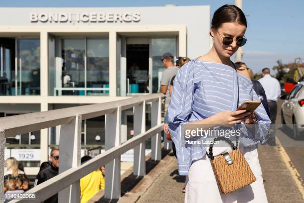 A guest wearing blue striped top and white pants at MercedesBenz Fashion Week Resort 20 Collections on May 16 2019 in Sydney Australia
