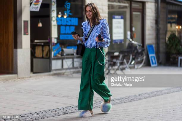 A guest wearing blue white striped blouse green pants sandals outside Busnel on August 30 2017 in Stockholm Sweden
