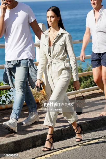 Guest wearing boiler suit and Coach clutch at Mercedes-Benz Fashion Week Resort 20 Collections on May 16, 2019 in Sydney, Australia.