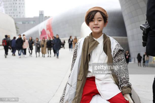 Guest wearing brown beret leopard rain coat white shirt and red pants is seen at the Hera Seoul Fashion Week 2019 F/W at Dongdaemun Design Plaza at...