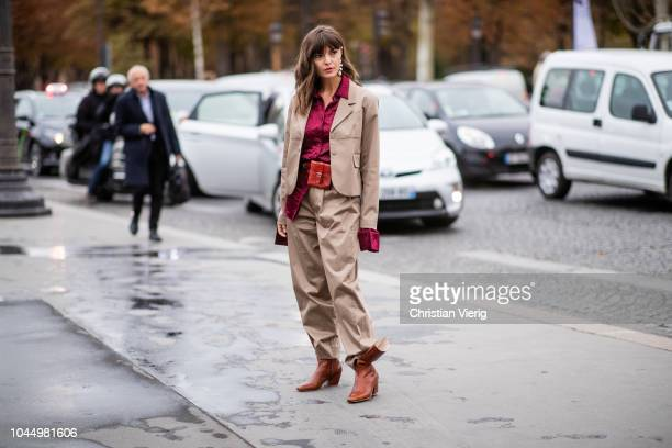 A guest wearing brown boots beige brown suit belt bag red button shirt is seen outside Chanel during Paris Fashion Week Womenswear Spring/Summer 2019...