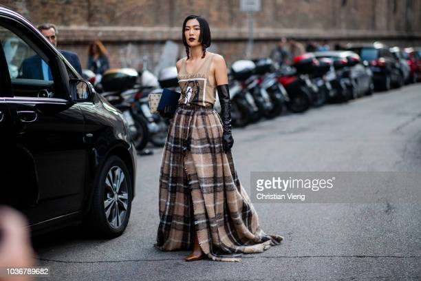 A guest wearing brown checked coat is seen outside Max Mara during Milan Fashion Week Spring/Summer 2019 on September 20 2018 in Milan Italy