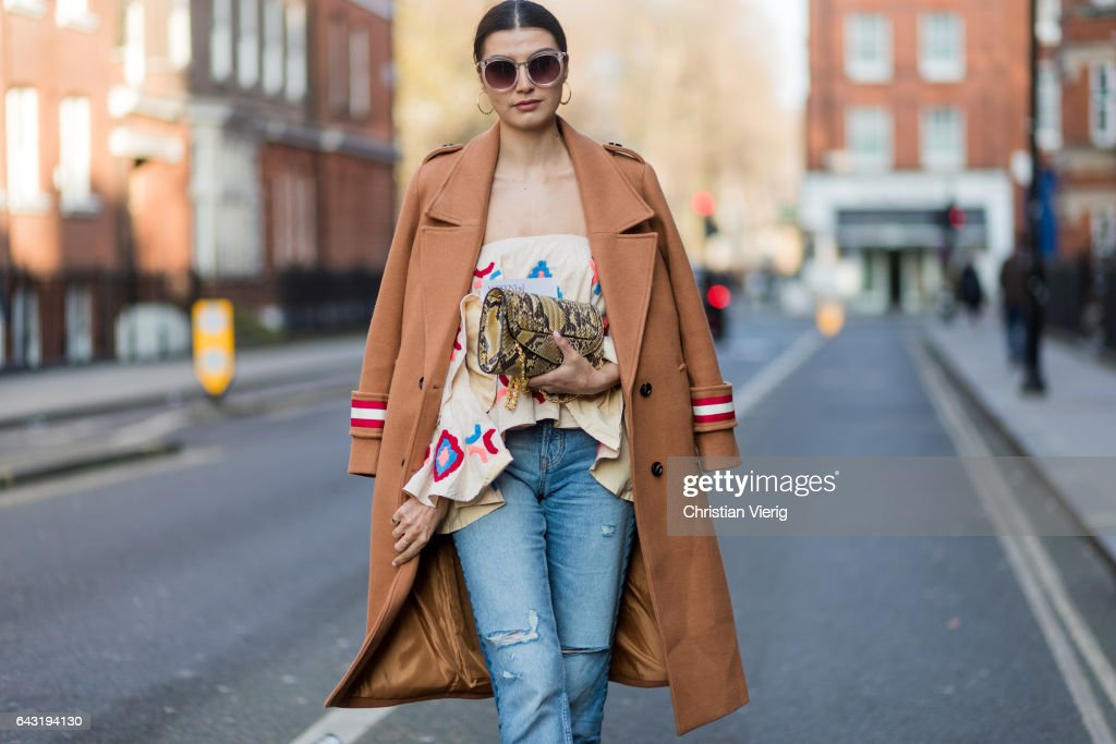 A guest wearing brown coat, denim jeans outside J.W. Anderson on day 2 of the London Fashion Week February 2017 collections on February 18, 2017 in London, England.