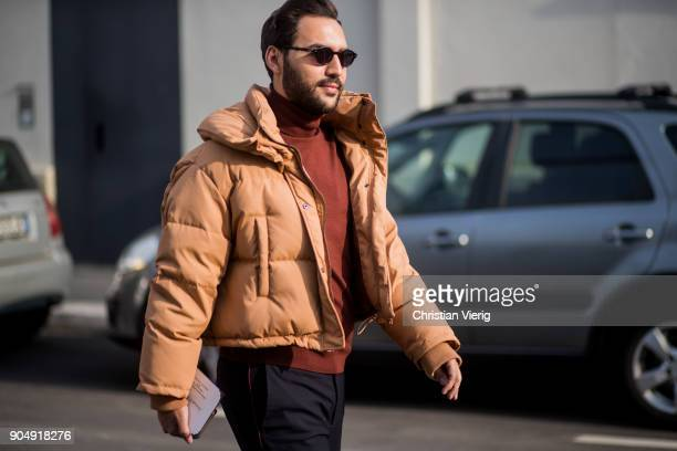 A guest wearing brown down feather jacket is seen outside DSquared2 during Milan Men's Fashion Week Fall/Winter 2018/19 on January 14 2018 in Milan...