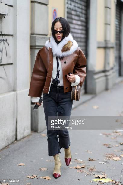 A guest wearing brown leather jacket fur scarf round Louis Vuitton bag is seen outside Marni during Milan Fashion Week Fall/Winter 2018/19 on...