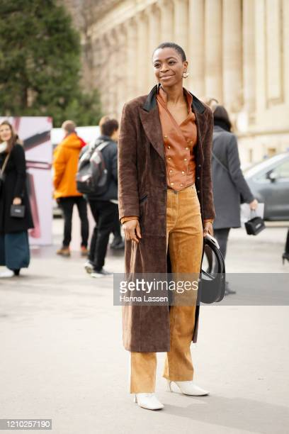Guest wearing brown suede trench, leather vest and white boots outside the Chanel show during Paris Fashion Week Womenswear Fall/Winter 2020/2021 Day...