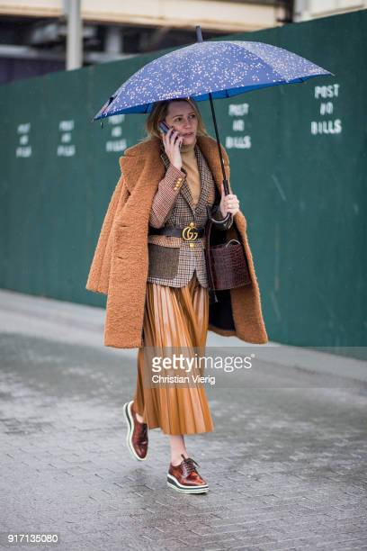 A guest wearing brown teddy coat brown midi skirt plaid blazer Gucci belt seen outside Tibi on February 11 2018 in New York City