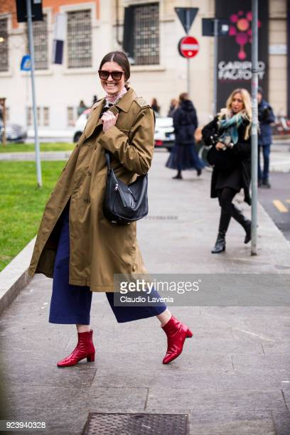 Guest wearing brown trench and red boots is seen outside Giorgio Armani show during Milan Fashion Week Fall/Winter 2018/19 on February 24, 2018 in...