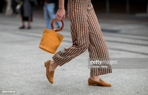 A guest wearing bucket bag button shirt with animal print flared pants with dot print loafers during MercedesBenz Fashion Week Resort 19 Collections...