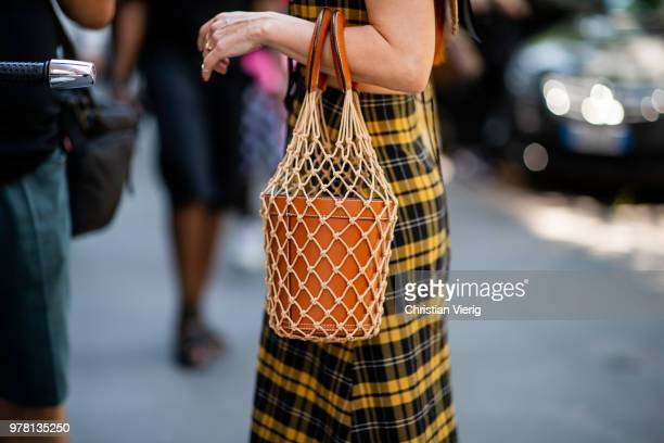 A guest wearing bucket bag is seen outside Fendi during Milan Men's Fashion Week Spring/Summer 2019 on June 18 2018 in Milan Italy