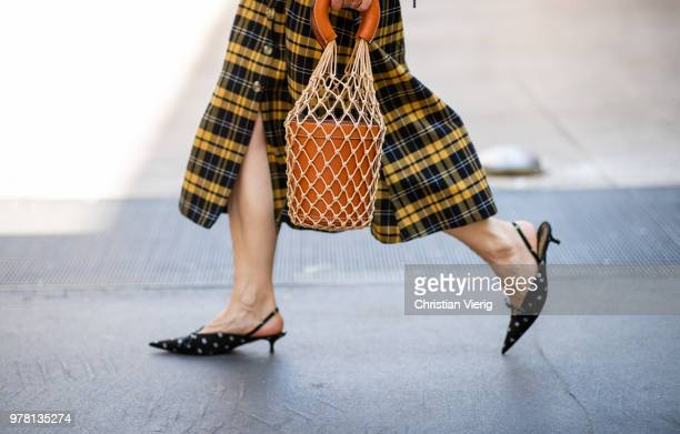 A guest wearing bucket bag pointed flats is seen outside Fendi during Milan Men's Fashion Week Spring/Summer 2019 on June 18 2018 in Milan Italy