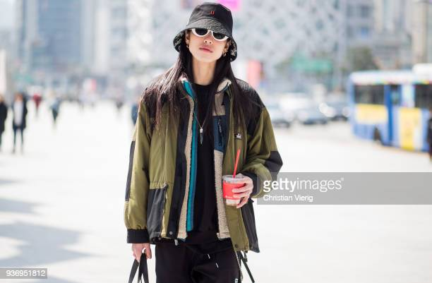 A guest wearing bucket hat checked jogger pants is seen at the Hera Seoul Fashion Week 2018 F/W at Dongdaemun Design Plaza on March 23 2018 in Seoul...