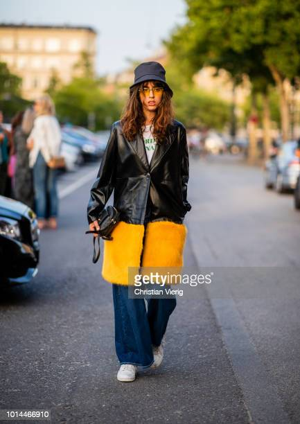 A guest wearing bucket hat leather coat wide leg denim jeans seen outside Saks Potts during the Copenhagen Fashion Week Spring/Summer 2019 on August...