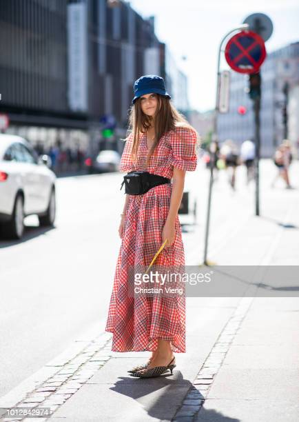 A guest wearing bucket hat salmon colored checked dress Prada belt bag pointed heels is seen outside Blanche during the Copenhagen Fashion Week...