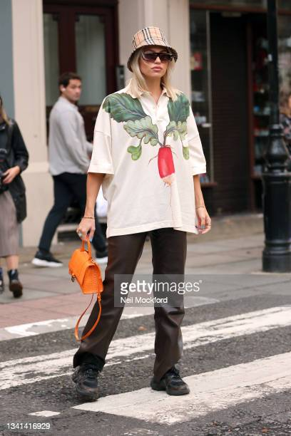 Guest wearing Burberry hat, printed t-shirt, orange purse attends Erdem at The British Museum during London Fashion Week September 2021 on September...