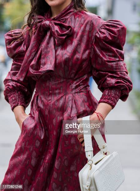 Guest wearing burgundy leather snakeskin dress with oversized bow and puff sleeves on September 06 2019 in New York City