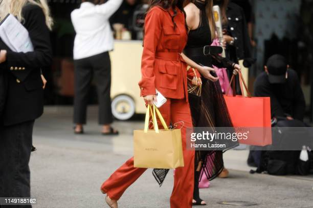 Guest wearing burnt orange suit at Mercedes-Benz Fashion Week Resort 20 Collections on May 15, 2019 in Sydney, Australia.