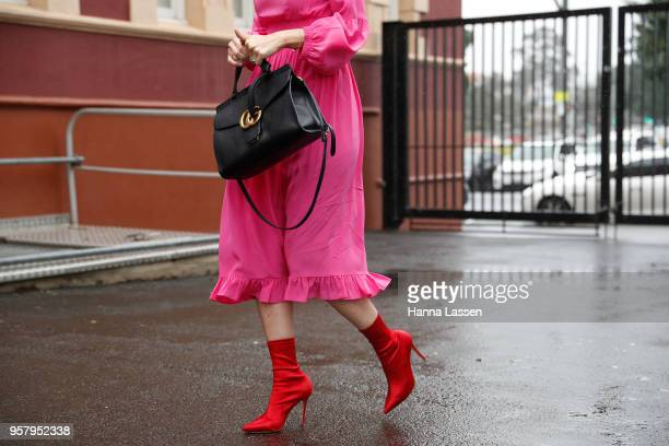 A guest wearing Camilla and Marc dress Gucci bag and red sock boots during MercedesBenz Fashion Week Resort 19 Collections at Royal Hall of...