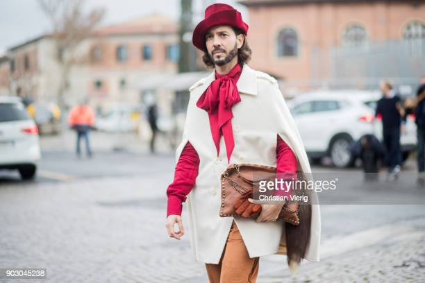 A guest wearing cape red hat is seen during the 93 Pitti Immagine Uomo at Fortezza Da Basso on January 9 2018 in Florence Italy