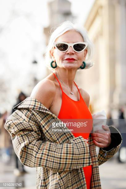 Guest wearing Celine sunglasses, orange top, plaid trench and white Bottega Veneta bag outside the Chanel show during Paris Fashion Week Womenswear...