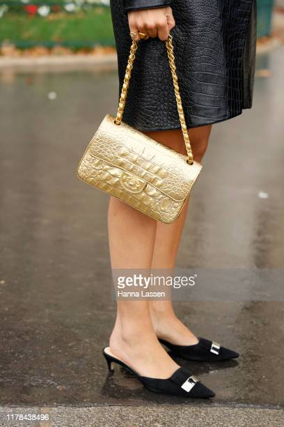 A guest wearing Chanel jacket and bag outside the Chanel show during Paris Fashion Week Womenswear Spring Summer 2020 on October 01 2019 in Paris...