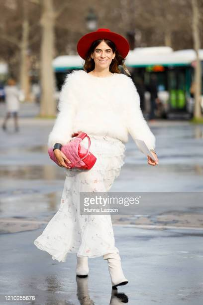A guest wearing Chanel pink bag red fedora white fluffy jumper white leather boots and maxi skirt outside the Chanel show during Paris Fashion Week...
