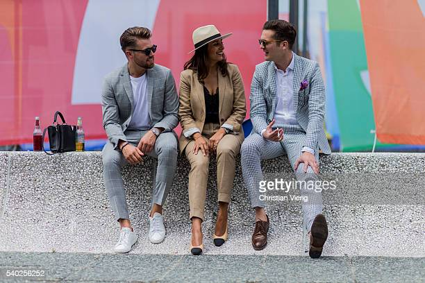 A guest wearing Chanel shoes and a beige suit and hat and a guest wearing a grey plaid suit during Pitti Uomo 90 on June 14 in Florence Italy