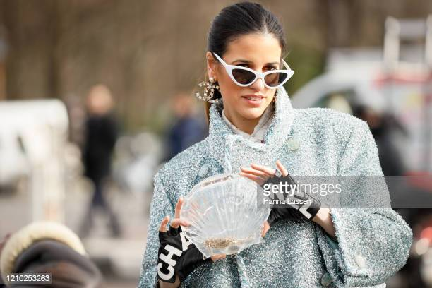 Guest wearing Chanel tweed jacket, mini skirt, shell shape clutch, Chanel earrings and black and white shoes outside Paris Fashion Week Womenswear...