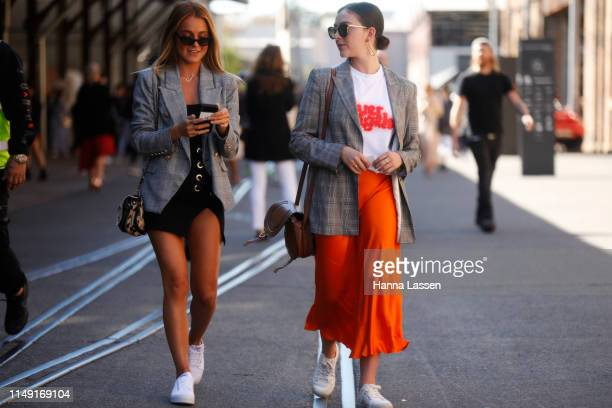 A guest wearing check blazer white shirt and orange silk skirt at MercedesBenz Fashion Week Resort 20 Collections on May 15 2019 in Sydney Australia