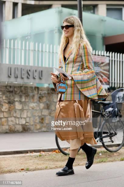 Guest wearing check flared blazer, deep apricot silky midi skirt and Loewe bag outside Loewe during Paris Fashion Week - Womenswear Spring Summer...