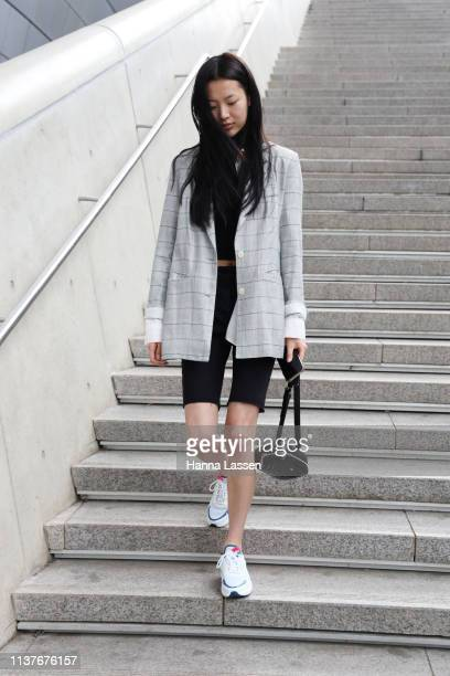 Guest wearing check grey blazer, bike shorts and Nike sneakers is seen at the Hera Seoul Fashion Week 2019 F/W at Dongdaemun Design Plaza at...