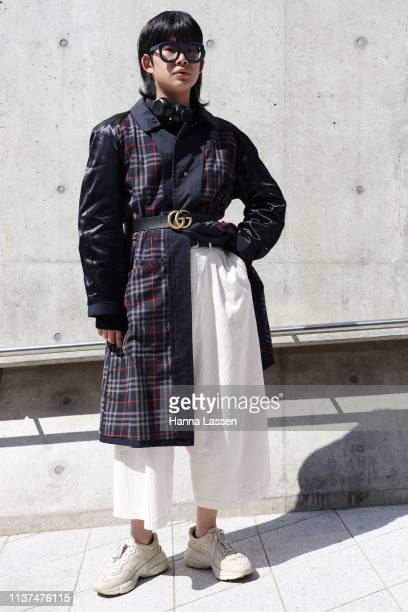 Guest wearing check trench coat white wide pants Gucci belt and Adidas sneakers is seen at the Hera Seoul Fashion Week 2019 F/W at Dongdaemun Design...