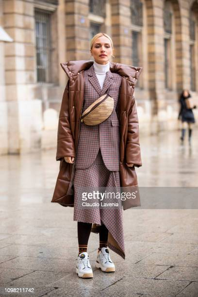 A guest wearing checked blazer with matching midi skirt white sneakers beige Balenciaga fanny pack and brown long jacket is seen outside Alexis...