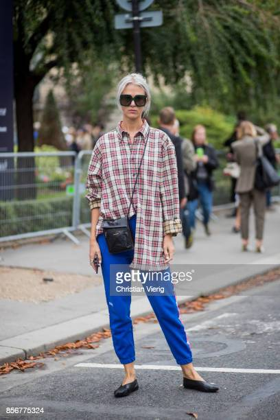 A guest wearing checked button shirt blue track suit pants seen outside Sacai during Paris Fashion Week Spring/Summer 2018 on October 2 2017 in Paris...