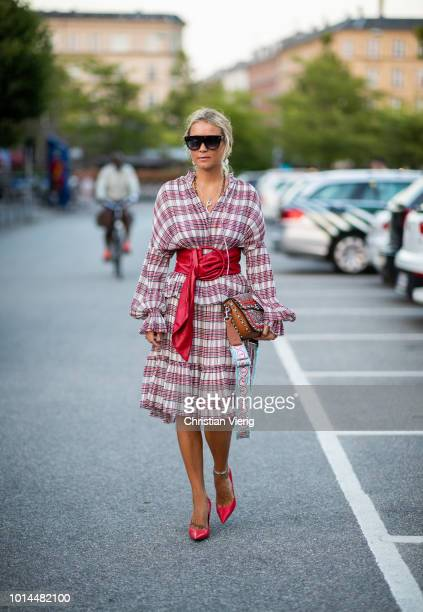 Guest wearing checked dress with belt, Valentino bag is seen outside Saks Potts during the Copenhagen Fashion Week Spring/Summer 2019 on August 9,...