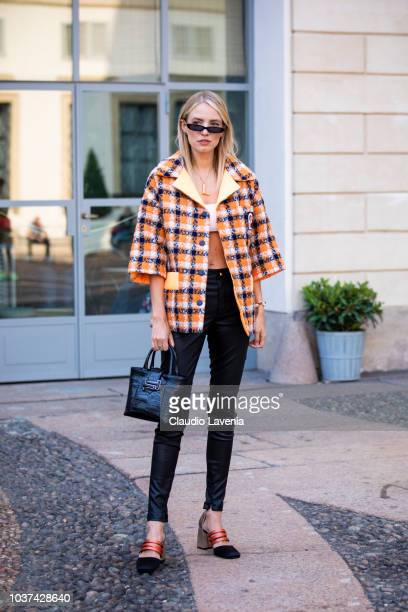 A guest wearing checked orange and black jacket black pants and Tod's black bag is seen before the Tod's show during Milan Fashion Week Spring/Summer...
