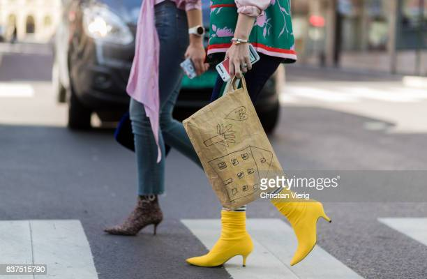 A guest wearing clutch and yellow sock boots outside Moods of Norway on August 22 2017 in Oslo Norway