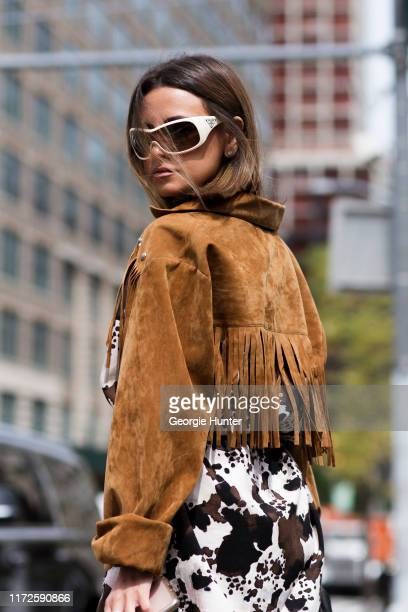 Guest wearing cow hide print dress Prada sunglasses and tan suede fringed cropped jacket on September 05 2019 in New York City