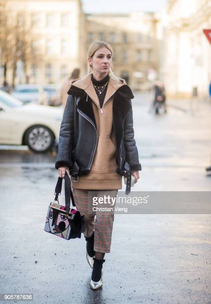 A guest wearing cropped checked pants beige hoodie black leather jacket is seen outside Der Berliner Modesalon during the Berlin Fashion Week January...