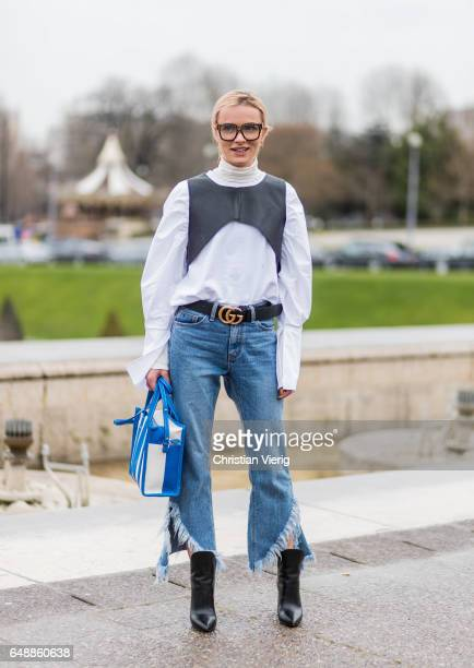 A guest wearing cropped denim jeans Balenciaga bag ankle boots glasses outside Hermes on March 6 2017 in Paris France