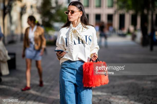 A guest wearing cropped denim jeans is seen outside Michael Olestad during Oslo Runway SS19 on August 15 2018 in Oslo Norway